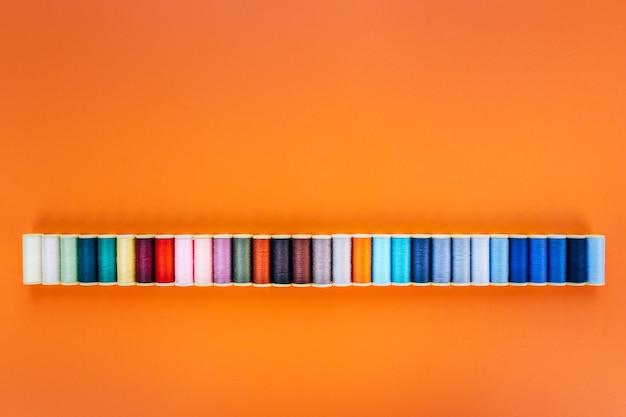 Szerokie tło panoramiczne z kolorowymi szpulami bawełny do szycia na pomarańczowym tle