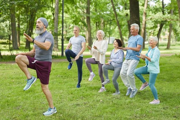 Szerokie ujęcie aktywnych starszych mężczyzn i kobiet wykonujących poranny trening w parku ze starszym trenerem