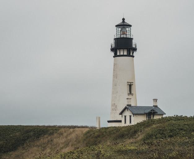 Szerokie ujęcie biało-czarnej latarni morskiej w pobliżu domu na szczycie wzgórza