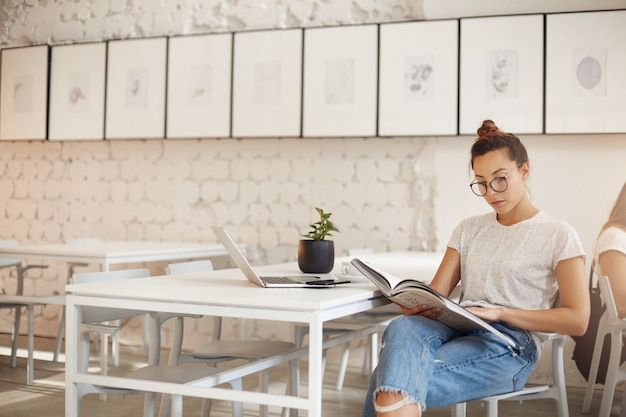 Szerokie ujęcie blogerki modowej patrzącej na magazyn przygotowujący swoje posty w mediach społecznościowych