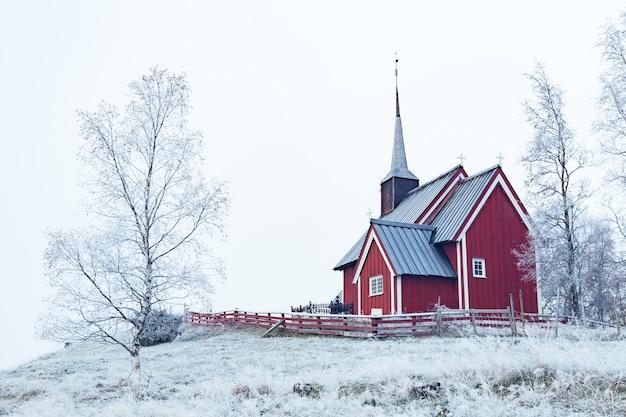 Szerokie ujęcie czerwonego budynku w zaśnieżonej okolicy otoczonej nagimi drzewami pokrytymi śniegiem pod bezchmurnym niebem