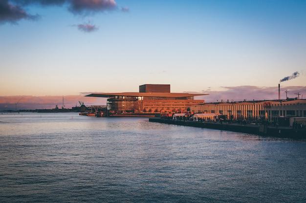 Szerokie ujęcie kopenhaskiej opery i ulicznych targów spożywczych przy zbiorniku wodnym