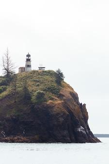 Szerokie ujęcie latarni morskiej i małej kabiny na klifie