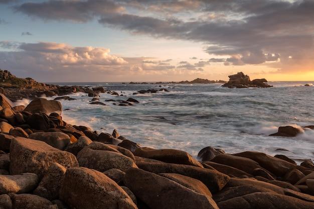 Szerokie ujęcie oceanu z formacjami skalnymi przy brzegu podczas zachodu słońca przy zachmurzonym niebie
