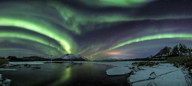 Szerokie ujęcie odbicia zorzy polarnej w jeziorze otoczonym przez pokryte śniegiem pola