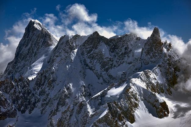 Szerokie ujęcie ogromnego szczytu całkowicie pokrytego śniegiem, zapierające dech w piersiach