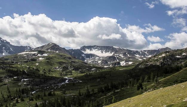 Szerokie ujęcie pasma górskiego z drzewami wokół i grubą warstwą chmur na niebie