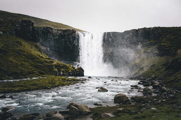 Szerokie ujęcie pięknego wodospadu w zielonych wzgórzach