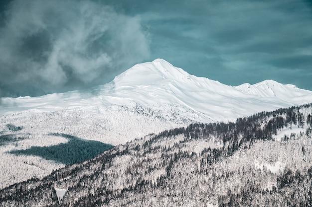 Szerokie ujęcie pięknych pokrytych śniegiem gór pod zachmurzonym niebem