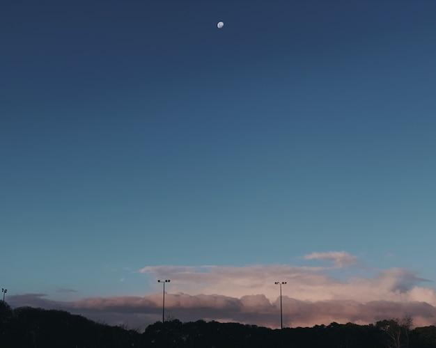 Szerokie ujęcie półksiężyca na niebie nad szarymi chmurami