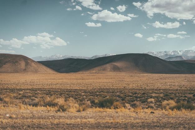 Szerokie ujęcie pustynnej doliny ze wzgórzami i górami