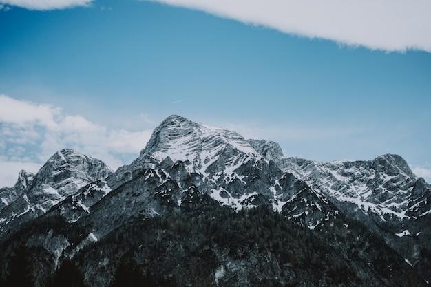 Szerokie ujęcie skalistych gór pokrytych śniegiem i piękne błękitne niebo w tle