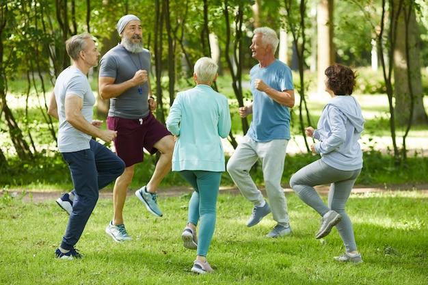 Szerokie ujęcie starszych mężczyzn i kobiet rozpoczynających poranny trening w parku z rozgrzewką