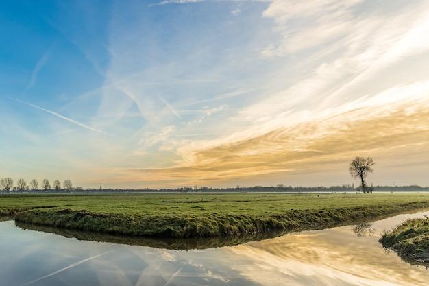 Szerokie ujęcie trawiastego pola z akwenem wodnym odbijającym piękny zachód słońca i niebo