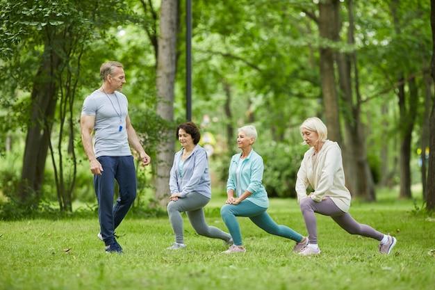 Szerokie ujęcie trzech przystojnych starszych kobiet po treningu w parku miejskim z trenerem patrząc na nich