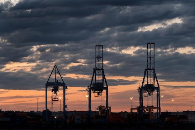 Szerokie ujęcie trzech wież w porcie podczas zachodu słońca w pochmurny dzień