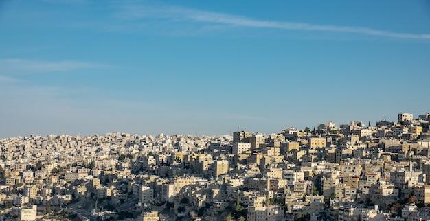 Szerokokątne ujęcie kilku budynków w mieście pod bezchmurnym niebem