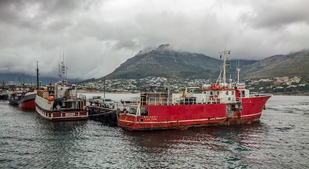 Szerokokątne ujęcie kilku statków na wodzie za górą pod pochmurnym niebem