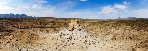 Szerokokątne ujęcie piaszczystej doliny ze skałą pośrodku