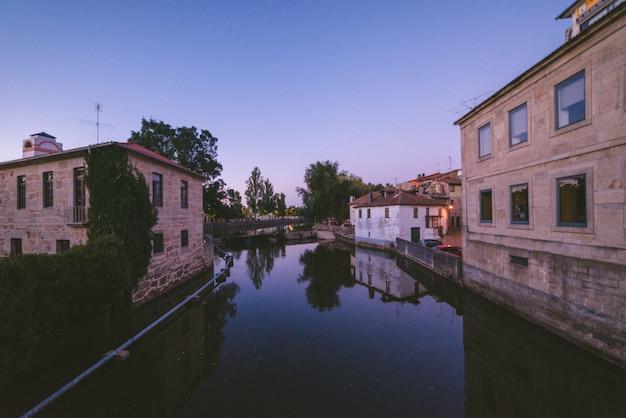 Szerokokątne ujęcie rzeki przepływającej przez miasto otoczone budynkami