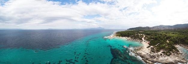 Szerokokątne ujęcie skalistego wybrzeża morza egejskiego z zielenią wokół, krzewami i drzewami, wzgórzami i górami, błękitną wodą z falami, widok z drona grecja