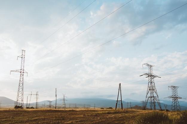 Szerokokątne ujęcie wielu słupów elektrycznych na suchym krajobrazie pod zachmurzonym niebem