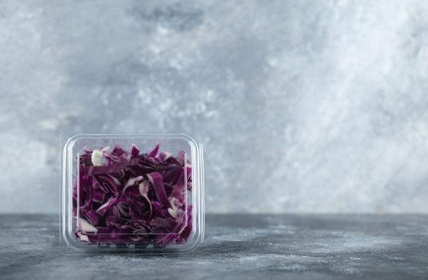 Szerokokątne zdjęcie plastikowego pojemnika pełnego posiekanej fioletowej kapusty o szarym tle.