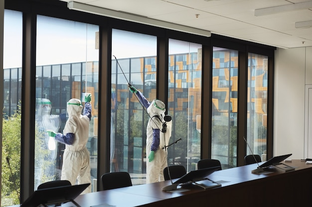 Szerokokątny portret dwóch pracowników ubranych w kombinezony do dezynfekcji okien biurowych w sali konferencyjnej,