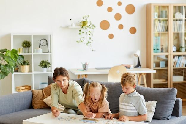 Szerokokątny portret kochającej rodziny ze specjalnymi potrzebami dziecka bawiącego się razem w puzzle i gry planszowe w domu, miejsce na kopię