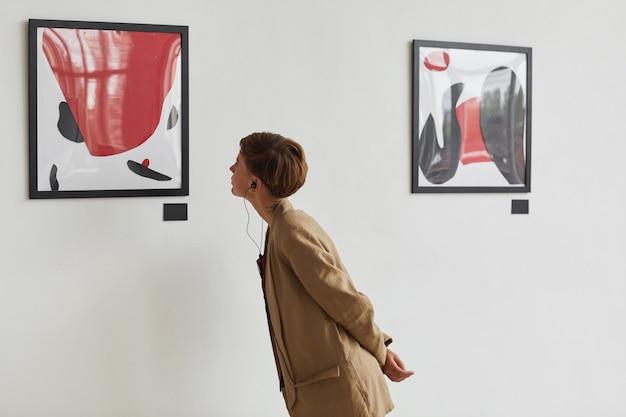 Szerokokątny portret wytatuowanej młodej kobiety oglądającej obrazy i słuchającej audioprzewodnika na wystawie w galerii sztuki współczesnej,