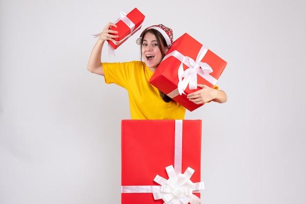 Szerokoooka Dziewczyna Z Santa Hat Trzyma Prezenty Stojące Za Wielkim świątecznym Prezentem Na Białym Tle Darmowe Zdjęcia