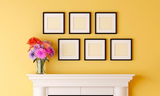 Sześć czarnych pustych ramek na żółtej ścianie pokoju ma wazon z kwiatami umieszczony na kominku.