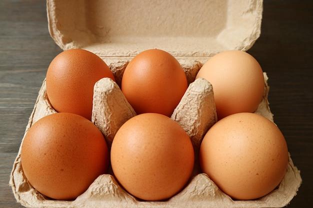 Sześć ekologicznych jaj kurzych w papierowym pudełku na ciemnobrązowym drewnianym tle