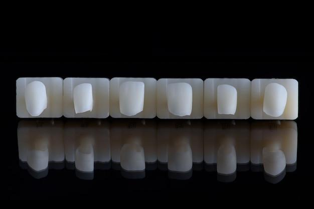 Sześć koron ceramicznych korony górnej szczęki na tle czarnego szkła sztuczna szczęka z