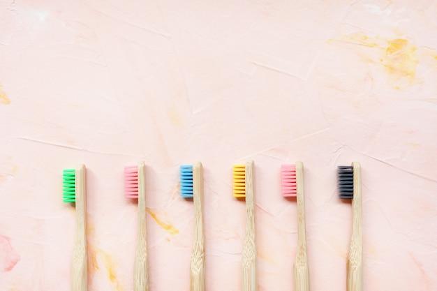 Sześć naturalnych drewnianych bambusowych szczoteczek do zębów. koncepcja bez plastiku i zero odpadów. widok z góry, różowy backgroundon, miejsce