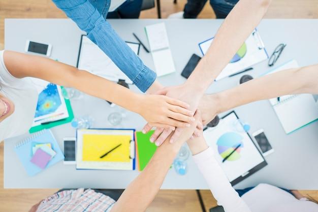 Sześć osób trzyma się za ręce przy biurku. widok z góry