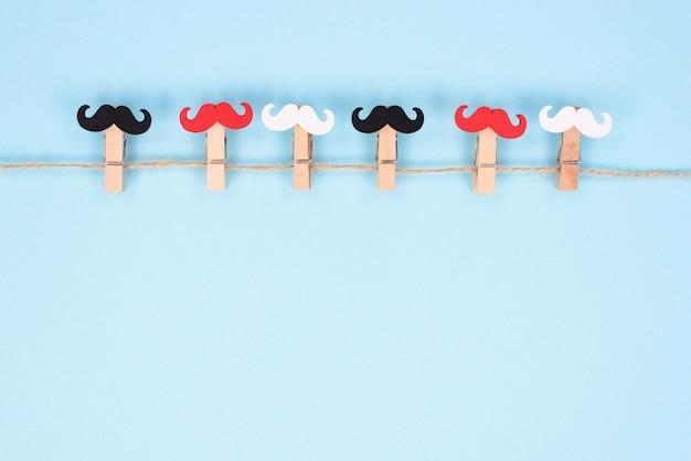 Sześć spinaczy do bielizny z różnym kolorem wąsy wiszące na liny na białym tle pastelowe