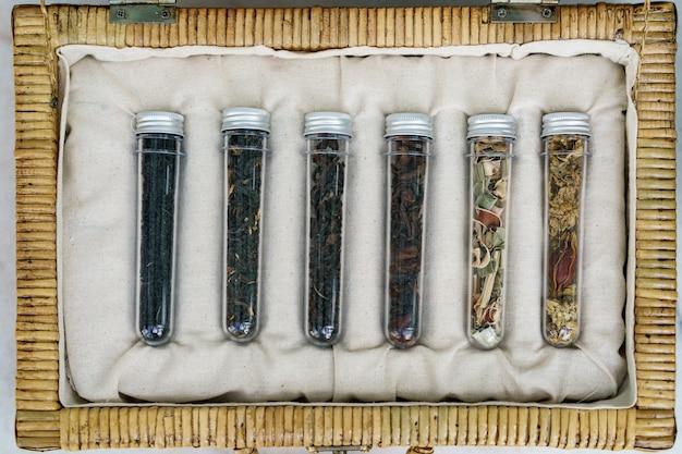 Sześć tubek różnych kolekcji herbat liściastych w wiklinowym koszu.