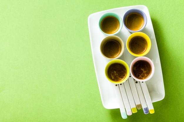 Sześć wielokolorowych filiżanek włoskiej kawy espresso z porcelanowymi łyżkami na talerzu do serwowania na zielonym tle.