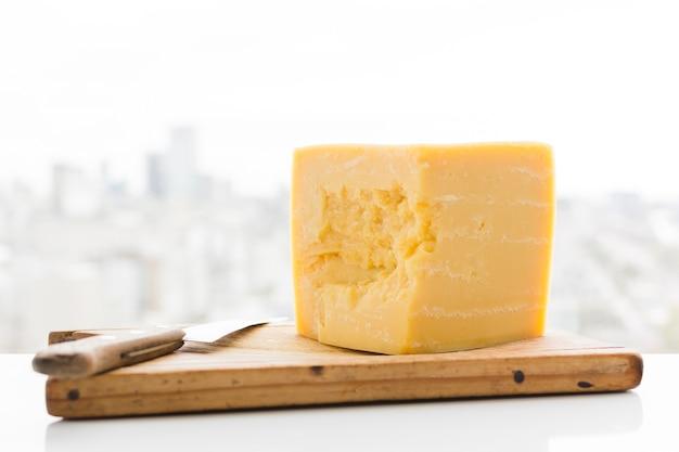 Sześcian sera cheddar z nożem na desce do krojenia nad biurkiem