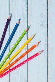 Sześciokolorowa tęcza od ołówków na niebieskim tle drewnianych
