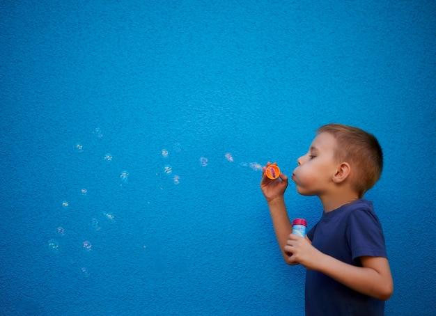 Sześciolatek z bańkami mydlanymi na niebieskim tle