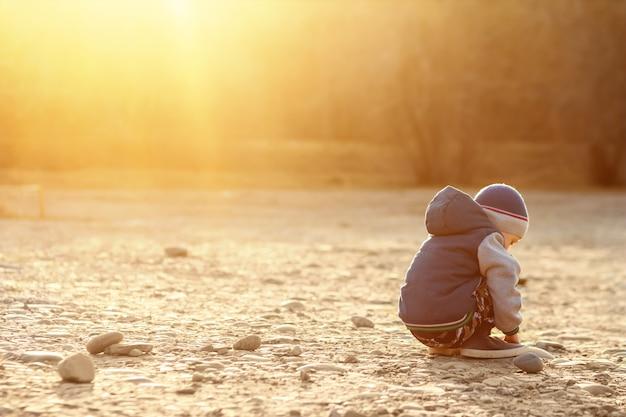 Sześcioletni chłopiec z autyzmem siedzi na ziemi sam o zachodzie słońca.