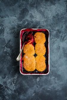 Szewc malin i czarnej porzeczki z lodami malinowymi w naczyniu do pieczenia. domowe ciasta owocowe. szare tło. widok z góry.