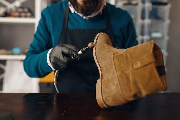 Szewc ostrzy podeszwę buta, naprawa obuwia