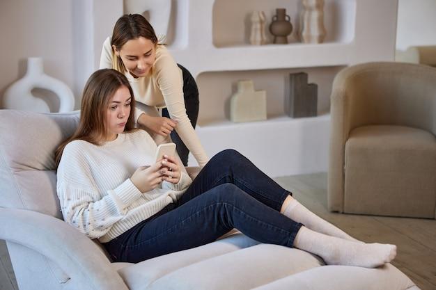 Szezlong z dwiema siostrami z telefonem na kanapie