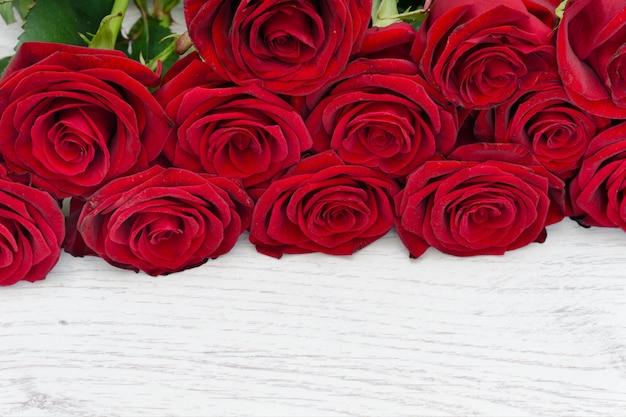 Szkarłatne róże na jasnym drewnianym tle.