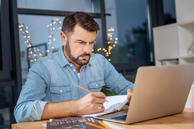 Szkice projektu. inteligentny, poważny, kreatywny projektant trzymający notebook i patrząc na ekran laptopa podczas rysowania nowego szkicu