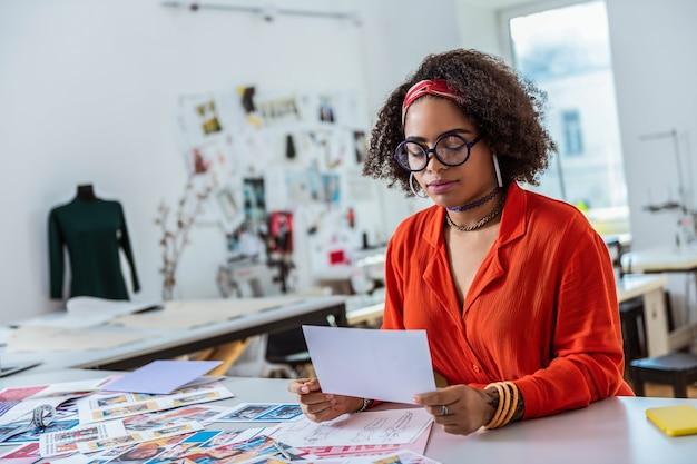 Szkice umieszczone do przodu. apelujący afroamerykanin niosący kartkę papieru koncentruje się na swojej pracy