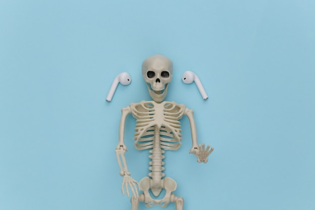 Szkielet i bezprzewodowe słuchawki na niebieskim tle.